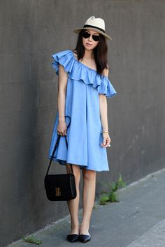 cute denim summer outfit with a ruffled off the shoulder chambray dress + black accessories that include black flats and a black purse + finished with a panama hat for a cute casual summer outfit