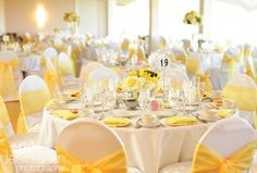 White table clothes, white chair covers, white napkins, yellow chair sashes…