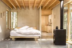 Inside, there's similarly understated material palette with concrete floors, plaster walls, and exposed hemlock rafters at the ceiling. #dwell #cabins #moderncabins #maine #tinyhomes