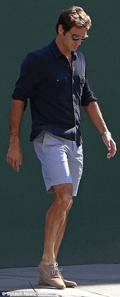 Daddy cool: The 33-year-old wore a navy shirt with pale blue shorts and suede beige shoes...