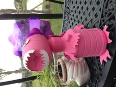 Recyclable dinosaur. School project made from juice and milk containers, paper plates and plastic cup with foil collar.