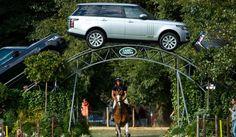 Jinete bajo un arco de vehículos Land Rover.