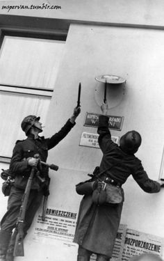 German troops removing the Polish emblem from the wall of a post office in Danzig, 1 Sep 1939 / Hans Sönnke