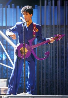 """Prince performs at the 46th Annual Grammy Awards in 2004 Please tell us who looks better in a purple zoot suit than Prince. Especially while playing his matching, custom guitar shaped like the """"Love Symbol,"""" which he took as his moniker from 1993 to 2000. Please! (Photo: Getty)"""
