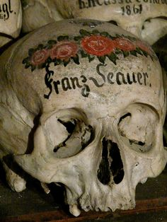 The Beinhaus (bone house) in Hallstatt dates back to the twelfth century AD. There are over 1200 skulls in the charnel, of them 610 have been painted in flowery designs, neatly stacked in rows along with next of kin and have the date of decease written on them.