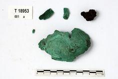 """Remains of textile rusted to pin on back of brooch (Viking) (T18953a) """"Ufullst. enkeltskallet skålspenne, bevart bare som irr uten metall under. Spennen tilhører den """"rene"""" typen R. 647, jfr. J. Petersen: Vikingtidens smykker fig. 37.1. Restene av nålefestet på baksiden er omgitt av fastrustete tekstilrester. Av spennen er nå bevart 2 stkr. 8,7 x 5,2 cm og 2,9 x 1,4 cm i tverrmål. Spennen må ha vært ca. 10,5 cm l. og ca. 6,5 cm br."""""""