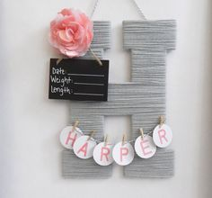 A 13.5 inch wooden single letter covered in a single color yarn, embellished with a flower or bow for girls and a star or bow tie for boys. Name