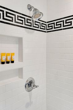 A black Greek key design adds a punch of contrast to this white subway tile shower, and a built-in niche stores shower essentials.