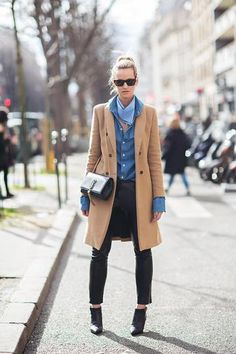 Classic wool camel coat over a blue shirt paired with leather pants and low cut ankle booties.