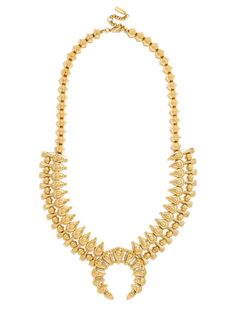 An oversized squash blossom done in antique gold is a fierce finishing touch.