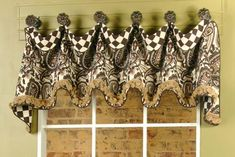 The valance is hung from decorative finials. The underlay of the valance was treated with 3 inches of the complementary fabric...
