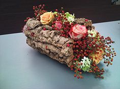 A lovely log design using moss as a medium making it a vegetative arrangement.