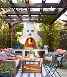 Mission Style patio on a California bungalow featuring a vine-wrapped pergola and outdoor fireplace