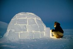 Kajutaq Avike, an Inuit hunter, about to enter an Igloo he has built at dusk. Northwest Greenland.