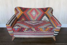 A kilim-upholstered loveseat. The modern lines provide a contrast with the traditional textiles – and also highlight the bold graphics of the design. Evelyn Loveseat from Kim Salmela. Design by This Way Home.