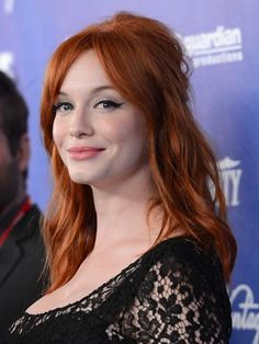 Christina Hendricks wavy half-up hairstyle with Brigitte Bardot volume and a flirty cat eye | allure.com