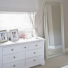 Clutter-free neutral bedroom with an oversized floor mirror