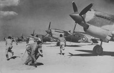 "British pilots running to their fighters P-40 ""Kittyhawk"" at the airport in North Africa"
