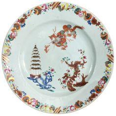 Assiette peinte d'un dragon et d'une pagode en porcelaine de Chine d'époque Qianlong Décorée dans les émaux de la famille rose, avec au centre un dragon poursuivant la perle enflammée, une pagode et un arbre fleuri. Sur l'aile, une frise d'ornements.
