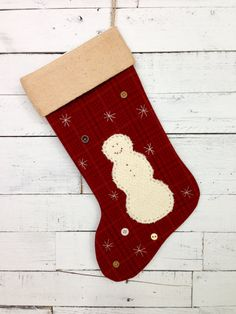~This is a red wool windowpane fabric stocking. It has faded gold and dark blue lines as the plaid. The backing fabric is the same as the front. ~The large snowman is a ivory color wool blanket remnant. It has lots of texture, which gives the snowman a fluffy look. ~The snowman is hand-sewn onto the stocking with light brown embroidery floss. ~The snowflakes are hand embroidered onto the stocking with ivory embroidery floss. ~The buttons are vintage buttons. ~The stocking is lined with…