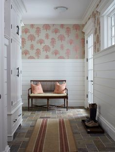 Shiplap siding serves as wainscoting in the mudroom entryway of this New Canaan, CT home by Michael Smith Architects.