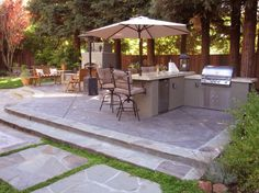 A two-level patio space was created using stamped, colored concrete with mortared flagstone accents.  A gas fireplace with pre-cast concrete capped seating was added, as well as an outdoor kitchen with bar counter.  The dryset flagstone patio with bistro seating creates a more intimate locale. / arborealis.com