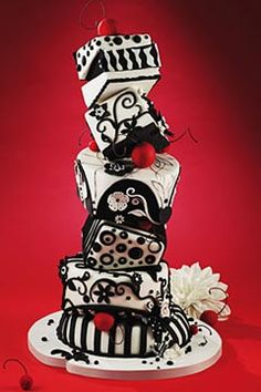 Black and white, whimsical five tier topsy turvy wedding cake decorated with black and white scrolls, patterns and shapes. Garnish with hand crafted large red cherries. From www.colettescakes.com