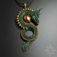Emerald green gold dragon pendant balroth made of toho and miyuki beads in metallic emerald green and shades of gold colors gold fire polish crystals as eyes of the dragon and brown seashell pearl lenght of the leather strap including the clasp 33 27 84 Beaded Jewelry Patterns, Embroidery Jewelry, Beaded Embroidery, Bead Jewellery, Seed Bead Jewelry, Wire Jewelry, Gold Dragon, Dragon Pendant, Beaded Animals