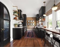 Kitchen with black cupboards, gold accents, and White subway tile
