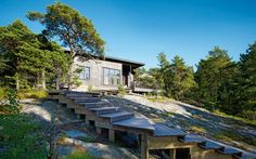 A wooden deck path leads down over the rocks to the sea from Anu and Andrew Shaw's summerhouse on the island of Själö. The couple wanted the timber to blend in with the landscape: the pine cladding was painted with a paint stain by Pinotex and the decking was treated with iron sulphide paint, which ages to a silvery-grey hue.