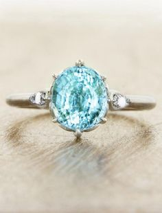 A one-of-a-kind piercing ocean blue Paraiba oval cut gem is flanked by marquis-shaped nooks accented with lustrous opals and diamonds for just the right amount of extra sparkle. by Ken & Dana Design.