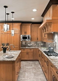 Pretty combo with the black hardware, stainless steel, marble countertops that continue up into the backsplash, fixtures, black molding.