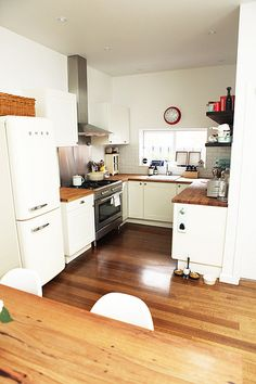 White smeg fridge (freezer on bottom), wood floors and countertops, white cabinets... stove should also be white.
