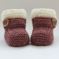 These snug little boots/bootees have been knitted  with  lovely Sirdar 30% wool blend yarn in deep rustic pink. They are edged with cream curly textured yarn and have a feature button strap across the front. This is for decoration only. They are warm a...