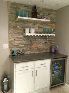 Small dry bar with Lowes Desert Quartz Ledge stone, floating shelves, hanging glasses rack, bar refrigerator...awesome!