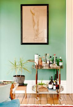Gold bar cart in green room with small indoor plant and sketch art