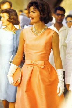 First Lady Jackie Kennedy wears a fitted silk apricot dress and triple strand of pearls while walking through crowds at Udaipur during her visit to India.