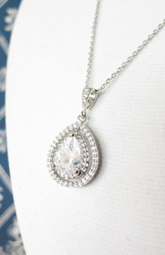 Silver necklace with a luxe halo style Clear Teardrop Cubic Zirconia drop, with two layers of cubic zirconia around the center teardrop. Simple wedding bridal necklace. brides. bridesmaids.