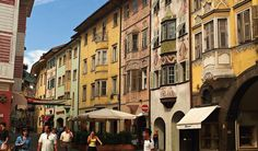 Reges Stadttreiben zwischen bunten Fassaden in Bozens Altstadt.