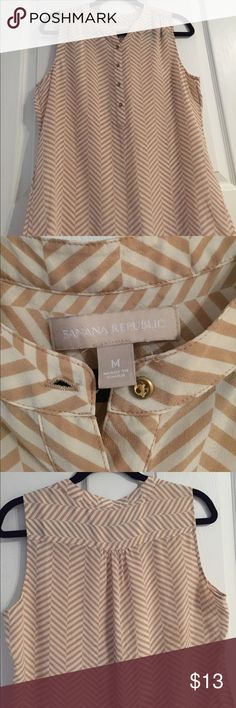 Banana Republic Tank Top A tan and ivory chevron tank. It is buttoned halfway down and has pleats. The last picture shows stains from possibly an iron. They are not noticeable unless you know what you're looking for. Banana Republic Tops Tank Tops