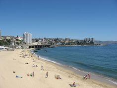 El ambiente es en una playa chilena. La señora esta relajando con su empleado cuando su hijo juega sobre la playa.