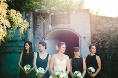 Bridesmaids pose in front of military ruins in Victoria, BC. Photo by Lara Eichhorn Photography.