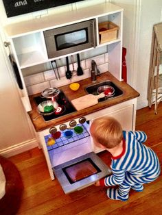 Ikea duktig play kitchen hack: butcher block effect to counter top, metallic spray paint to oven and microwave, realistic oven rack, knobs and hinge on stove. Wonderful!
