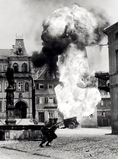 Two soldiers of the 101st Infantry Regiment dash past an explosion. Kronach, 1945