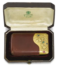 A Fabergé jewelled gold cigarette case, Moscow, 1899-1908. In Art Nouveau taste, the lid repoussé and chased with stylised leaves and set with a faceted emerald, blue sapphire, pale yellow sapphire and synthetic ruby, above engraved presentation inscription in Russian 'Ya. Yu. Gringaut/ a memento from your comrades in building / the Sarapulski Water Works and Electrical Plant/ January 1910', with leather pouchette, in original Fabergé leather case.