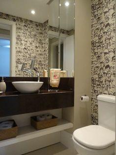 O banheiro social deste apartamento de 2 dormitórios no Bairro Petrópolis tornou-se um lavabo descontraído, com o papel de parede com caricaturas e o tampo em silestone marrom. Juliana Baumhardt Arquitetura