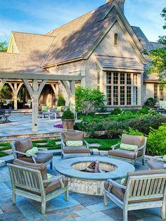sillones de madera rodean el lugar de fuego en el jardín