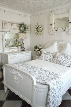 Shabby chic style white bedroom with gray and white linens on the bed