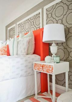 Gray design panels behind the bed are a great way to add interest to a bare wall. Makes a nice backdrop for bold orange and white color scheme.