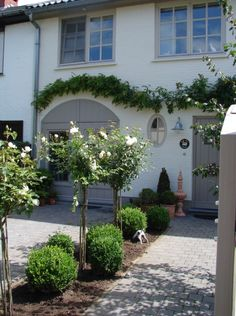 Love the soft grey trim and creamy house! Nice backdrop for the landscaping too!
